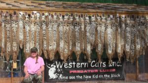 Western Cats inc image of Reilee Helms in front of trapping furs